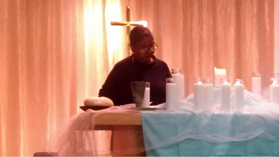 Aqueelah As-Salaam serving communion at Praxis' Easter Vigil